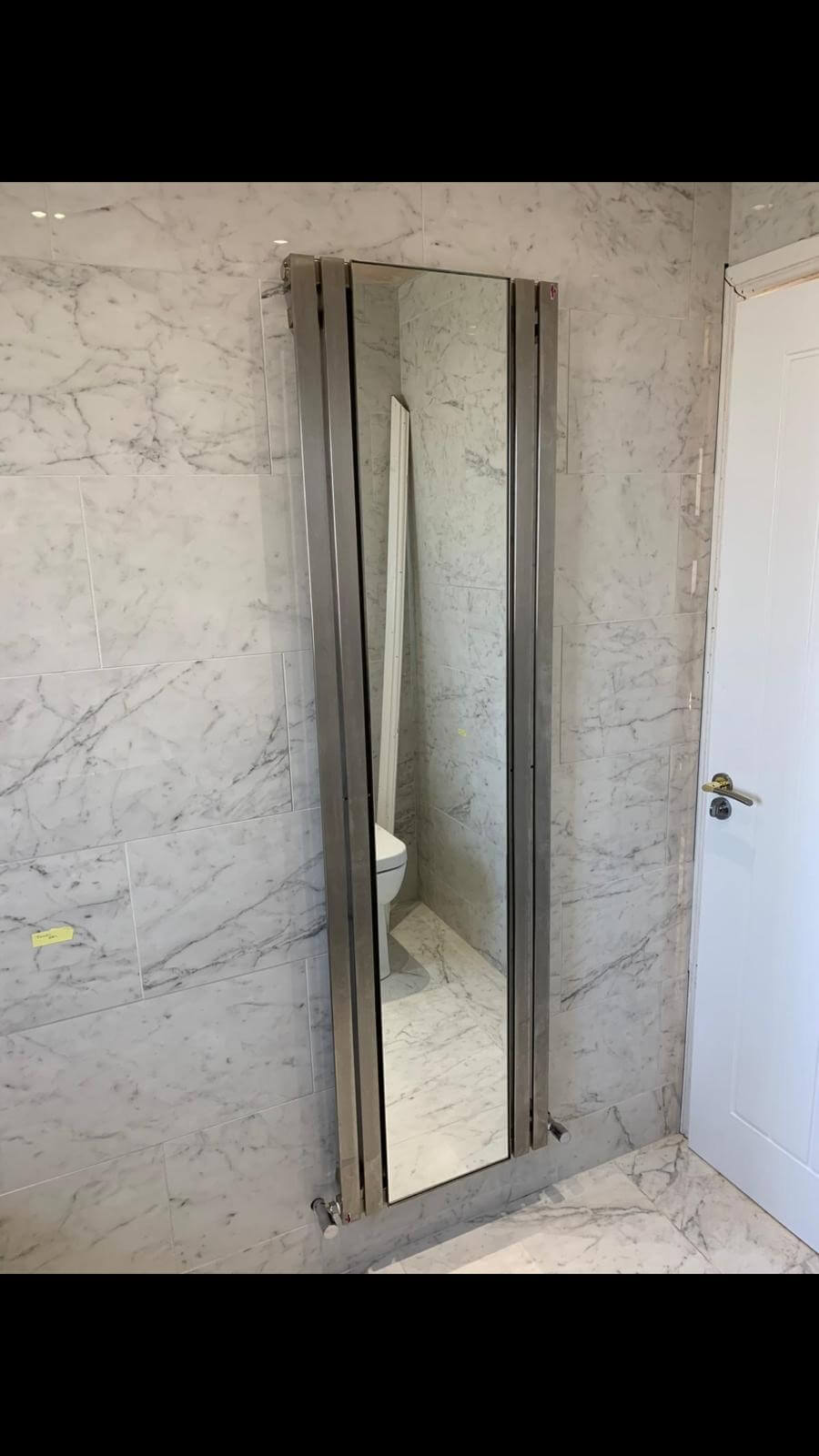 This image shows a standing radiator with a built in mirror, installed by Celsius Home Improvements as part of a bathroom renovation in Liverpool.
