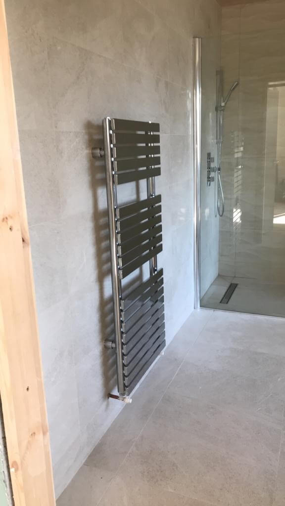 This image shows a standing radiator installed by Celsius Home Improvements as part of a bathroom renovation in Liverpool.