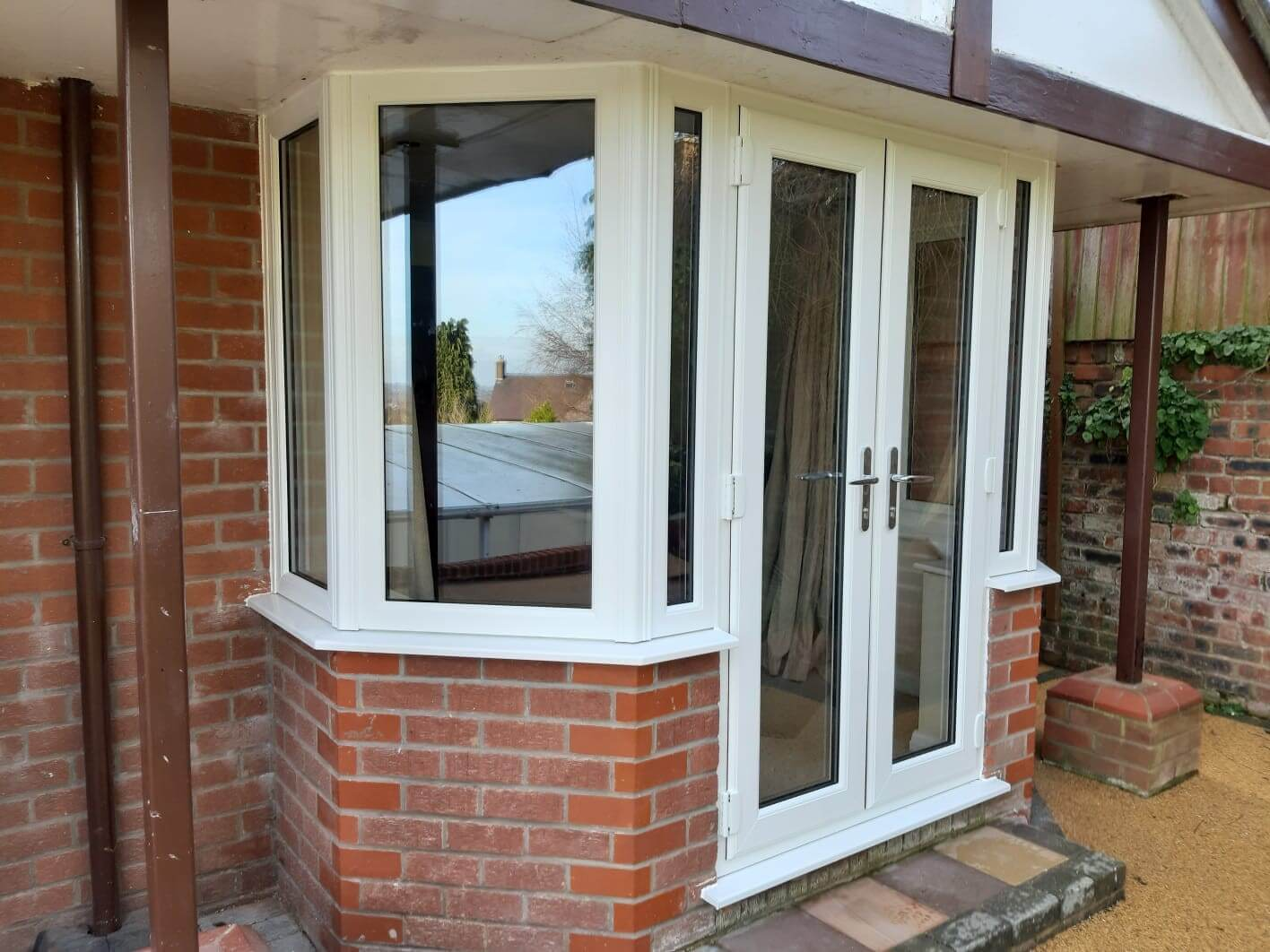 This image shows a bay window with aluminium frames in white with a French patio door.