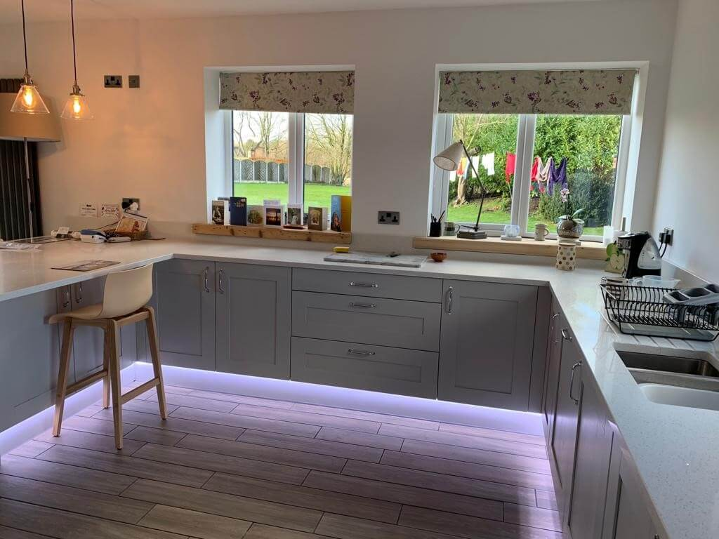This image shows a completed kitchen renovation along with living area and bi-folds in Formby, Merseyside, by Celsius Home Improvements.