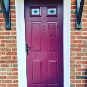 This image shows a new composite front door installed in Ellesmere Port, Cheshire by Celsius Home Improvements. The colour of the composite door is 'Very Berry'.