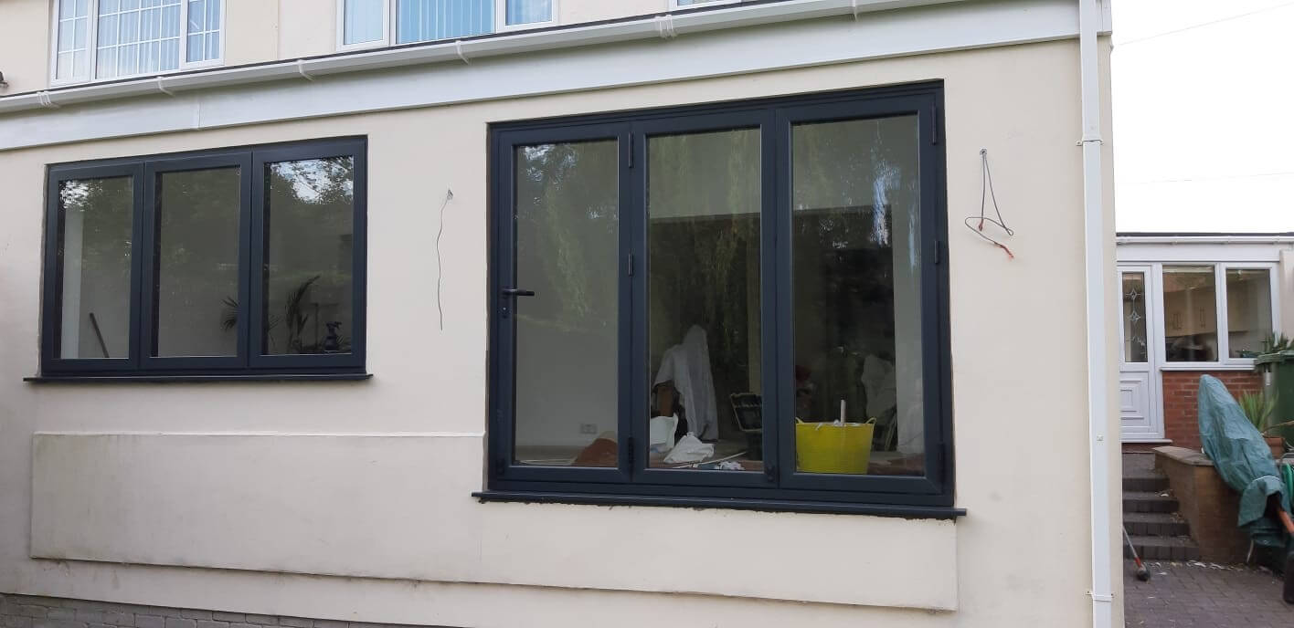 This image shows the external view of a anthracite grey aluminium bi-fold doors and 1 window in Melling, Merseyside. The installation was completed by Celsius Home Improvements.
