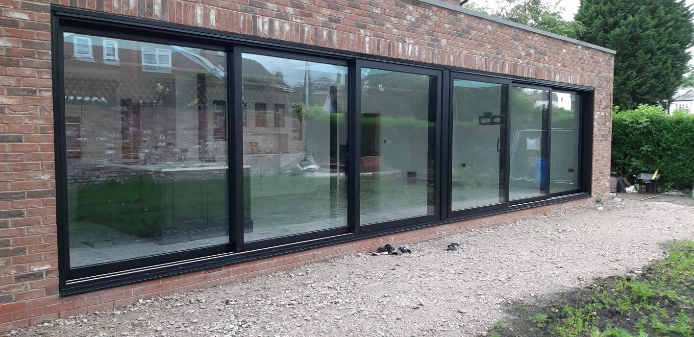 This image shows the completed installation of two sets of aluminium sliding patio doors installed by Celsius Home Improvements at a new build home in Aughton, Ormskirk.