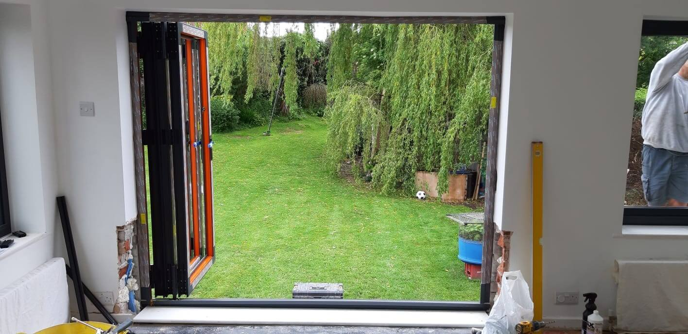 This image shows the installation of of an anthracite grey aluminium bi-fold door and window in Melling, Merseyside.