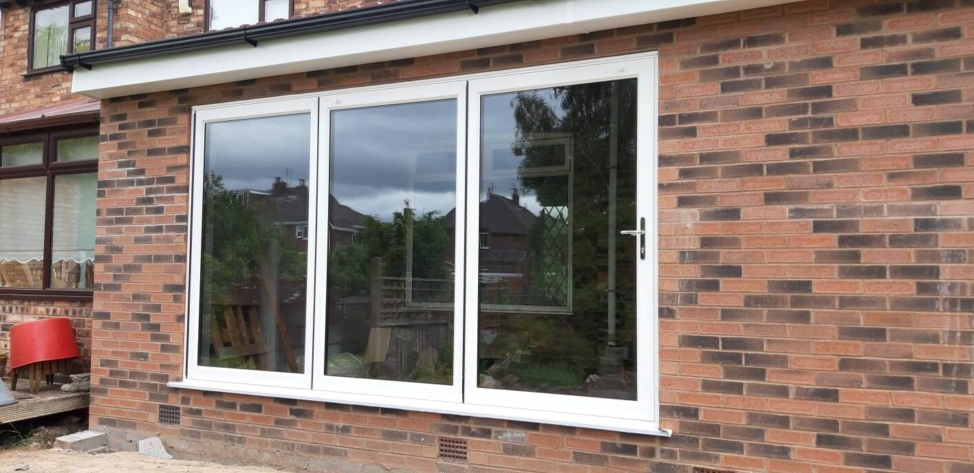 This image shows a white aluminium bi-fold door installation in Huyton, Liverpool. The installation was completed by Celsius Home Improvements.